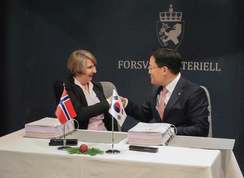 Son Jae-il, CEO of Hanwha Land Systems, shakes hands with Mette Elin Sørfonden, head of Norway's defense material agency, after a contract on K9 self-propelled howitzers. (image: Hanwha Land Systems)