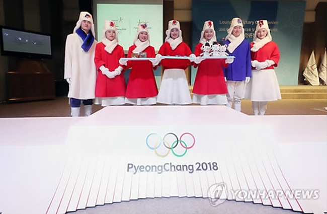 South Korean models wearing costumes for the victory ceremonies at the PyeongChang Winter Olympic and Paralympic Games pose for a photo behind the Olympic podium at an event in Seoul on Dec. 27, 2017. (Image: Yonhap)
