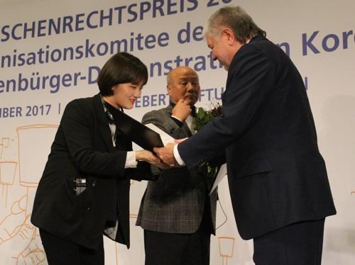 Jang Ae-jin (L), a survivor of the 2014 Sewol ferry sinking, receives the 2017 FES Human Rights Award from Kurt Beck, head of the German political foundation Friedrich-Ebert-Stiftung (FES), during a ceremony in Berlin on Dec. 5, 2017. (image: Yonhap)