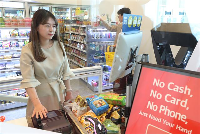 A Lotte official gives a demonstration of how to pay at its cashierless convenience store in Seoul with vein recognition technology. (image: Lotte Group)