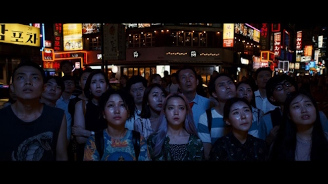 "Both scenes are essentially one and the same; anonymous South Koreans gaze upwards at a TV screen wearing expressions of shock and concern, while astute viewers will also notice in the background the korean words for ""king crab"" and ""pocha"" – a shortened version of the word pojangmacha, which means a drinking establishment. (Image: Lotte Entertainment)"