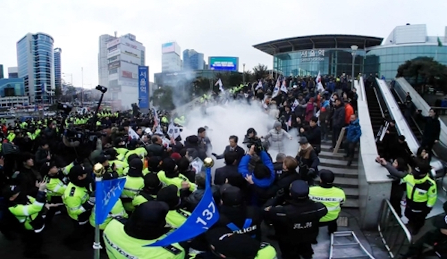 "Chanting slogans such as ""Kim Jong-un's Pyongyang Olympics"", a right-leaning activist group held a rally in the public square in front of Seoul Station, where its members burned the North Korean flag and a picture of Kim Jong-un. (Image: Yonhap)"