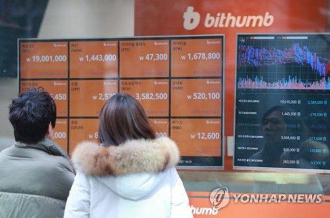 Two people read tables displayed at Bithumb, the largest cryptocurrency exchange in South Korea, in central Seoul on Jan. 11, 2018. (Image: Yonhap)
