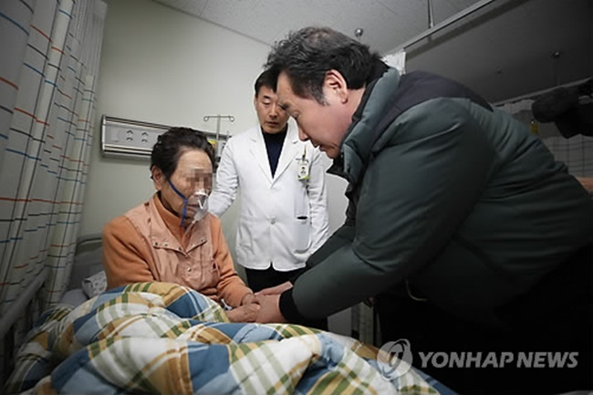 Prime Minister Lee Nak-yon holds the hands of an elderly woman injured in a hospital fire in South Korea's southeastern city of Miryang on Jan. 26. (Image: Yonhap)