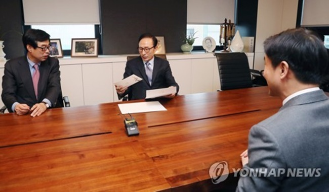 Former President Lee Myung-bak (c) reviews written invitations in his Seoul office from the International Olympic Committee and incumbent President Moon Jae-in to official events of the PyeongChang Winter Olympic Games, including the opening and closing ceremonies of the games, after receiving the invitations from the presidential office on Jan. 31, 2018. (Image: Yonhap)