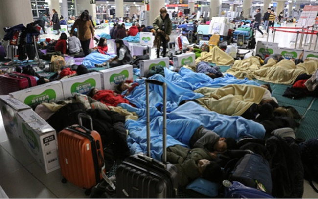 Tourists sleep in the lobby of Jeju International Airport on the southern resort island of Jeju on Jan. 12, 2018, as heavy snow and strong winds caused hundreds of flight cancellations and delays the previous day. (Image: Yonhap)