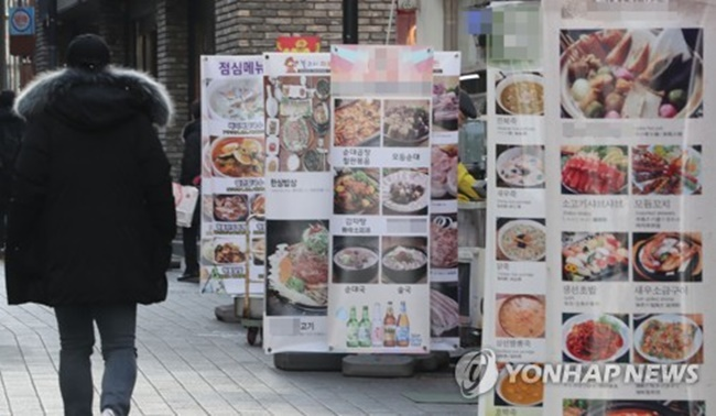 A citizen passes by menu signboards in downtown Seoul on Jan. 7, 2018. (Image: Yonhap)
