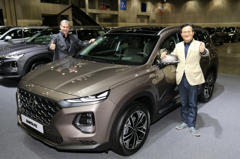 Luc Donckerwolke, head of Hyundai and Genesis Design Center, (L) and Lee Kwang-guk, the chief of Hyundai's domestic sales, pose for a photo beside the all-new Santa Fe SUV following its launch event at KINTEX exhibition hall in Ilsan. (image: Hyundai Motor)