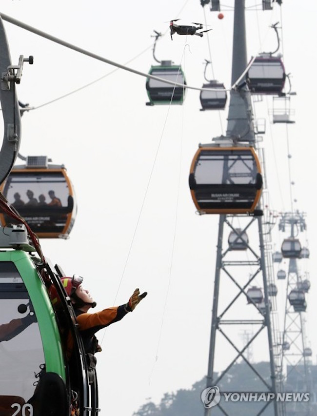 Once the operative arrived at the cable car, a drone holding a string attached to a rope floated up, and by pulling this string, the response team member was able to safely guide the trapped passengers down to the ground. (Image: Yonhap)