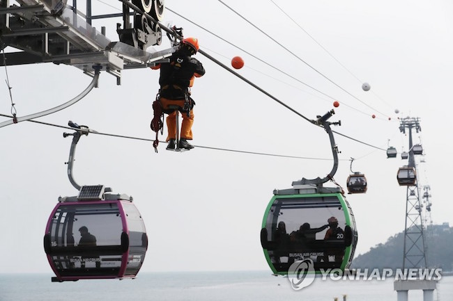 A member of the response team moved along the overhead line to reach the cable cars hanging in the air over water. (Image: Yonhap)
