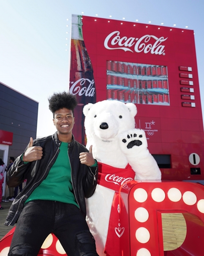 "Born to a Nigerian father and a Korean mother, the dark-skinned Han Hyun-min has earned the informal title of ""South Korea's first black model"", and was named to Time Magazine's ""The 30 Most Influential Teens of 2017"". (Image: Coca-Cola)"
