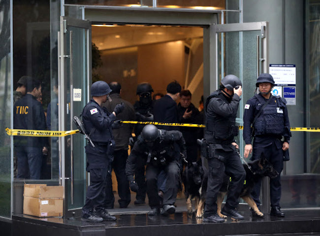 Police coming out of Samsung Life Insurance's corporate building after someone called in a bomb threat. (Image: Yonhap)