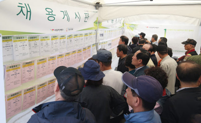 Individuals looking at job postings (Image: Yonhap)