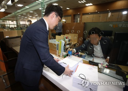 An official from Hannuri Law hands over documents related to its lawsuit against Apple Inc. and its local branch to the Seoul Central District Court in the nation's capital on March 30, 2018. (image: Yonhap)