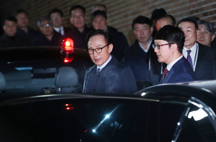 Former President Lee Myung-bak is escorted by prosecution officials from his house to a vehicle that will take him to a Seoul detention center on March 23, 2018. (image: Yonhap)