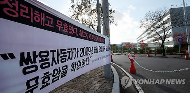 A banner demanding firings from 2009 be reversed (Image: Yonhap)