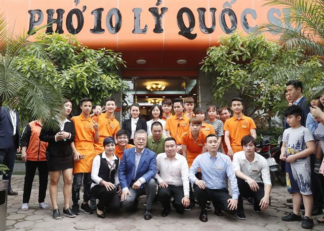 "South Korean President Moon Jae-in poses with employees of ""Pho 10 Ly Quoc Su,"" a rice noodle restaurant, in Hanoi on March 24, 2018. (image: Yonhap)"