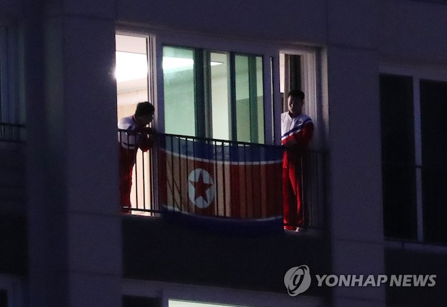 Photos of a North Korean flag hanging from the balcony of a residential building are catching the attention of passersby. (Image: Yonhap)