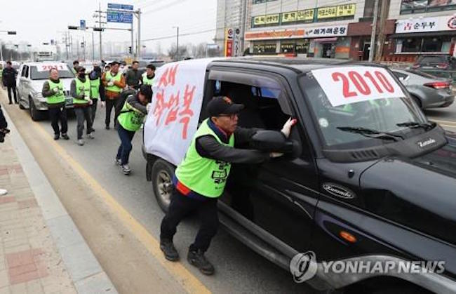 "The rally, which consisted of a 2km march to the gates of Ssangyong Motor's Pyeongtaek plant, was christened by the participants as ""The Clanging Cowbell of the Fired"". (Image: Yonhap)"