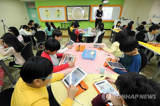 According to the Ministry of Education, starting this year, children in the third and fourth grades and in the first year of middle school will be given digital textbooks – electronic tablets with an internet connection for downloading educational content. (Image: Yonhap)