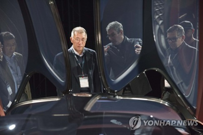 Hyundai Motor's Vice Chairman Chung Eui-sun, flanked by top car designers, examines the Genesis Essentia concept at an international motor show. (Image: Yonhap)