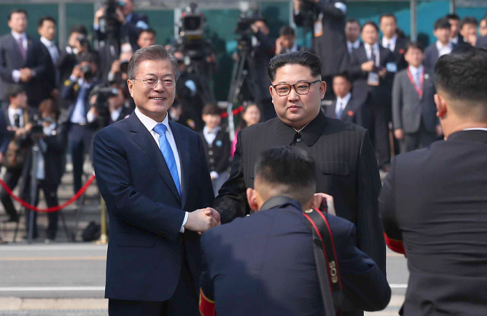 South Korean President Moon Jae-in (L) and North Korean leader Kim Jong-un shake hands after Kim crossed the inter-Korean border at the Joint Security Area of Panmunjom on April 27, 2018 for a meeting with Moon that marked the third inter-Korean summit. (image: Yonhap)