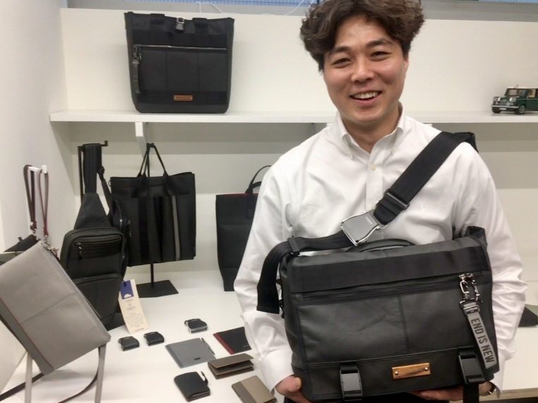 Choi Ian, head of South Korean bag maker Morethan, poses for a photo at his office in Seoul with one of the company's Continew bags made with car seat leather and a seat belt. (image: Yonhap)