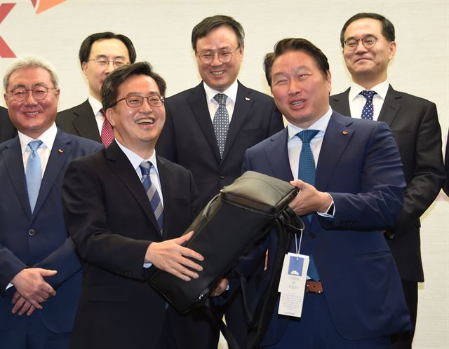 SK Chairman Chey Tae-won (R) hands over a Continew bag to Finance Minister Kim Dong-yeon (L) after a meeting at the conglomerate's headquarters in Seoul on March 14, 2018. (image: Min. of Strategy & Finance)