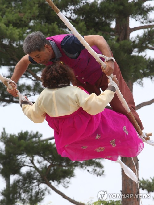 "A couple ride on a swing as part of the Gangneung Danoje Festival in Gangneung, Gangwon Province, on June 19, 2018. The festival has been designated one of the ""Masterpieces of the Oral and Intangible Heritage of Humanity"" by UNESCO. (Yonhap)"