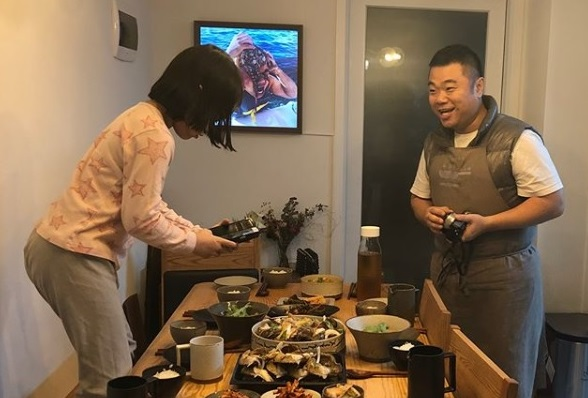 Jeong Jong-chul(R) and his daughter taking a photo of dinner prepared by Jeong. (image: Jeong Jong-chul)