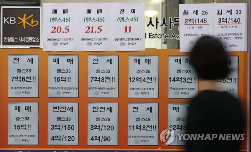 In this file photo taken on July 1, 2018, a passerby walks in front of a realtor's office displaying signs for home leases and home sales. A sign shows the sale price of a 148-square-meter apartment near in Gangnam district is 2.05 billion won (US$1.8 million). (image: Yonhap)