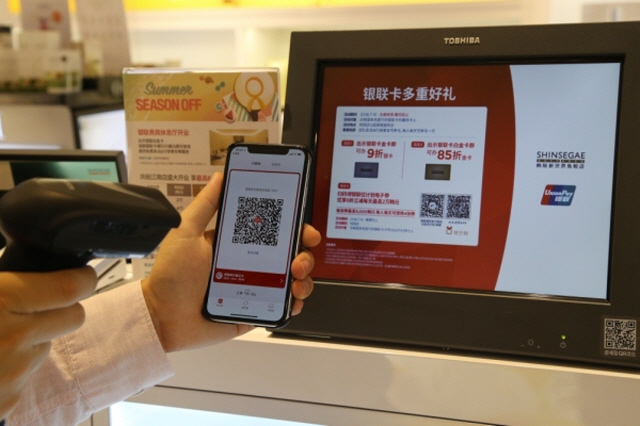A model showcases how to use the UnionPay QR code payment system. (image: Shinsegae DF Inc.)