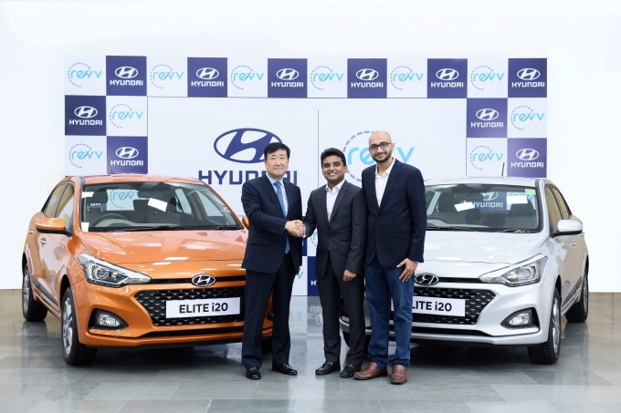Hyundai Motor India CEO Koo Young-key (L) shakes hands with Revv co-founder Anupam Agarwal (C), with another Revv co-founder, Karan Jain, standing beside them after they discussed measures to cooperate in the mobility business in Indian Quality Center on Aug. 17, 2018. (image: Hyundai Motor)