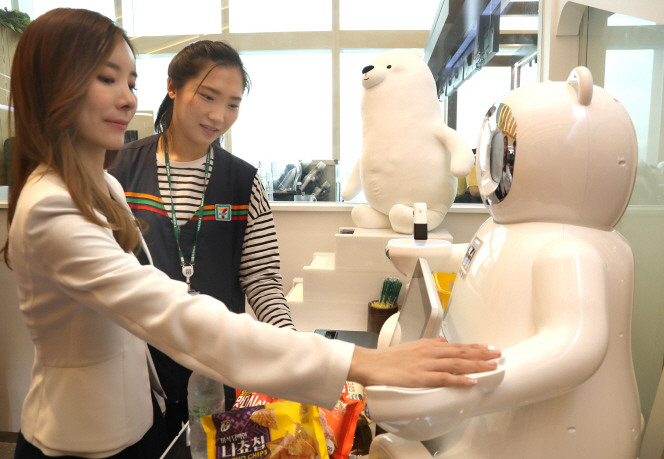 A model poses for a photo to show the function of Veny, a robot that allows customers to pay without cash or credit cards based on vein recognition technology, at a 7-Eleven store in Seoul on Aug. 28, 2018. (image: Yonhap)