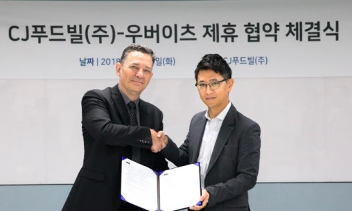 Jean-Marc Serayssol (L), head of Asia Sales at Uber Eats, shakes hands with a CJ Foodville executive at the signing ceremony of a partnership in Seoul on Aug. 28, 2018. (image: Uber Eats)