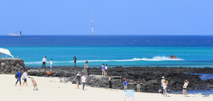 Tourists walk on Gwakji Beach on the southern resort island of Jeju. (image: Yonhap)
