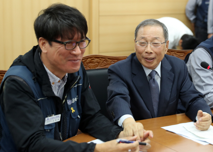 SsangYong Motor CEO Choi Jong-sik (R) holds hand of Kim Deuk-joong, chief of SsangYong Motor branch of the Korean Metal Workers' Union, after signing an agreement to rehire 119 fired workers by 2019. (image: Yonhap)