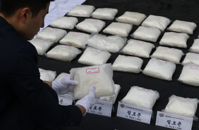 An investigator shows bags of methamphetamine, which are part of the 112 kilograms of the drug that the police confiscated, at the Seoul Metropolitan Police Agency on Oct. 15, 2018. (image: Yonhap)