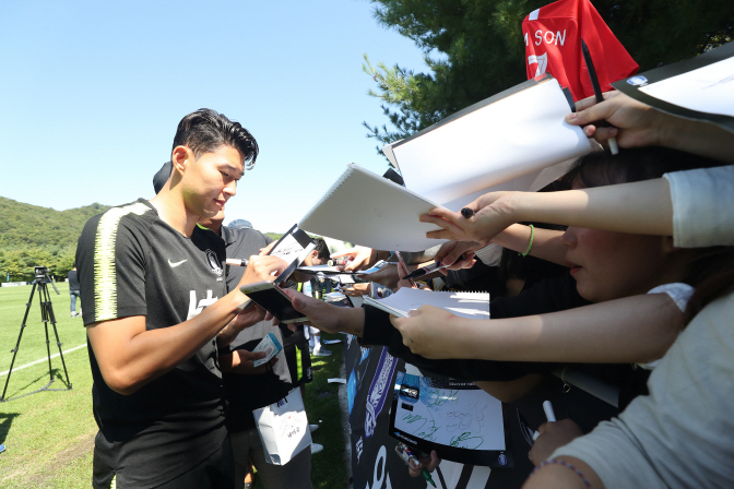 South Korean football player Son Heung-min (L) signs his autograph for fans at the National Football Center in Paju, north of Seoul on Sept. 8, 2018. (image: Yonhap)
