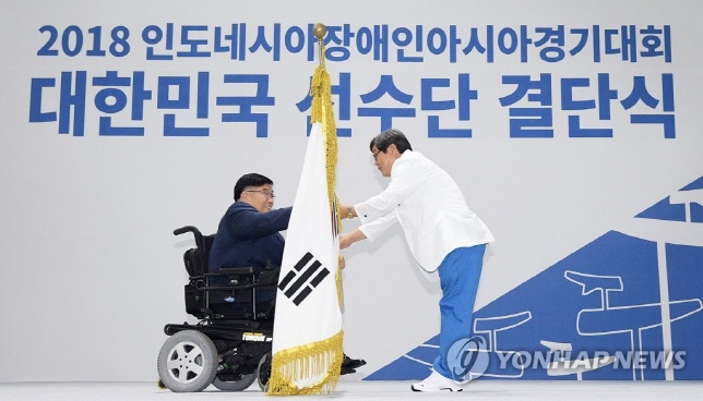 Korea Paralympic Committee (KPC) President Lee Myung-ho handing the national flag to Jun Min-sik, South Korea's chef de mission for the Asian Para Games in Indonesia, at the national team launching ceremony in Icheon, Gyeonggi Province on Sept. 19, 2018. (image: Yonhap)