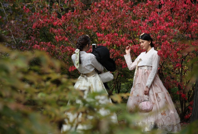 Tourists wearing the traditional Korean costume hanbok take pictures against a background of maples at Deoksu Palace in Seoul on Oct. 23, 2018. (Yonhap)