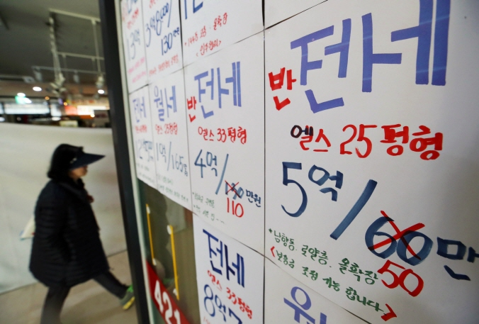 A woman walking past the office of a real estate broker in Seoul. (image: Yonhap)