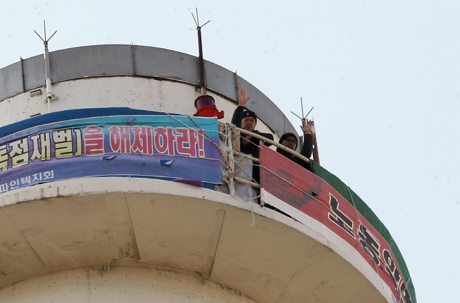 "Hong Gi-tak, a worker at FineTek and former leader of the union chapter, and secretary-general Park Jun-ho began their ""smokestack sit-in"" at the power plant in Seoul in November of last year. (image: Yonhap)"