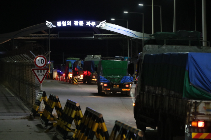Trucks wait in a row on a street before crossing into North Korea via the western land route on Nov. 29, 2018, to deliver 50 tons of chemicals to help it fight the spread of pine tree diseases. (Yonhap)