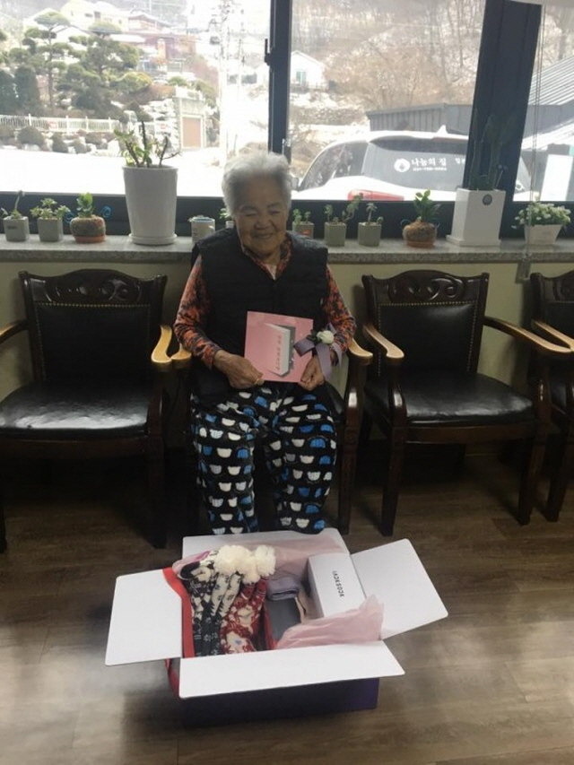 A former sex slave victim, who was forced to work at Japanese brothels during World War II, smiling at winter goods brought by BTS' fans. (image: The House of Sharing)
