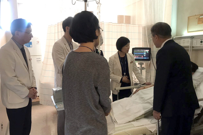 President Moon Jae-in (R) visits a finance ministry official who recently suffered a stroke while working late for the parliamentary passage of the government budget bill, at a Seoul hospital on Dec. 7, 2018. (image: Cheong Wa Dae)