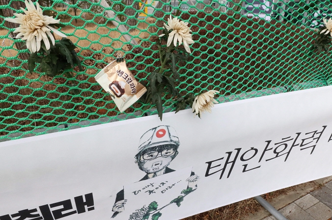 Chrysanthemum and pies hang on a net in front of the Korea Western Power Co.'s headquarter in Taean, 146 kilometers south of Seoul, on Dec. 16, 2018, to tribute the death of Kim Yong-kyun, a 24-year-old sub-contracted worker who was killed in a conveyor belt accident in the previous week. (Yonhap)
