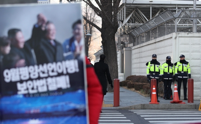 Police officers stand guard outside the U.S. Embassy in Seoul on Dec. 18, 2018, as a lone demonstrator holds a political picket across the street. (Yonhap)