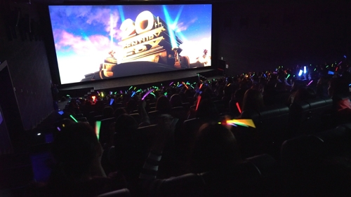 "South Korean moviegoers waving glow-in-the-dark sticks in the singalong screening of ""Bohemian Rhapsody"" on Nov. 24, 2018. (image: 20th Century Fox Korea)."