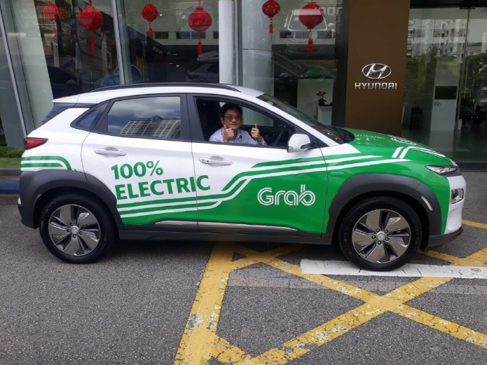 A driver giving a thumbs-up in a Kona EV used for Grab's ride-hailing services in Singapore. (image: Hyundai Motor Co.)